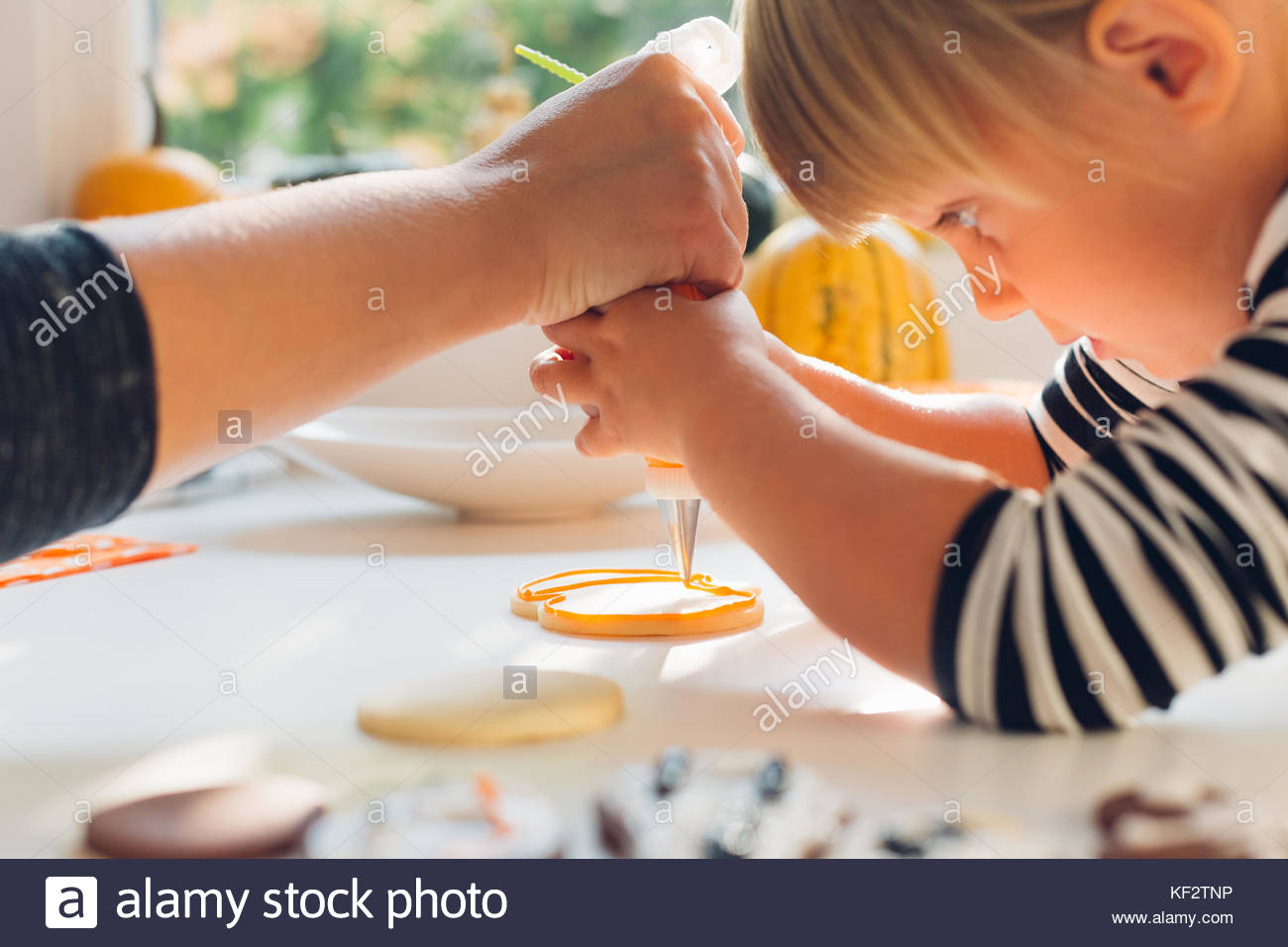 Closeup of Mom and Daughter decorating Halloween Cakes - Stock Image