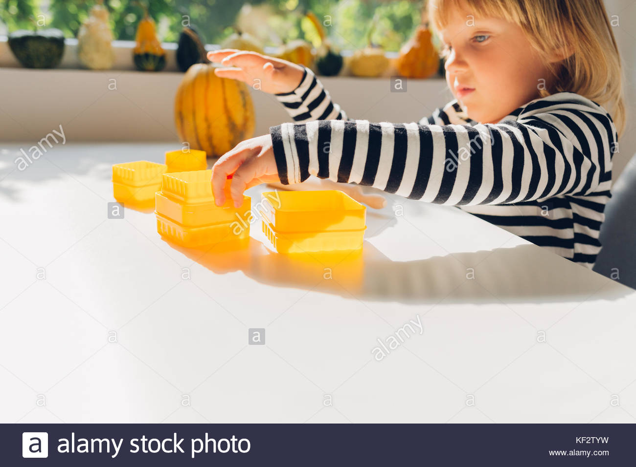 Girl is playing with molds for cakes - Stock Image