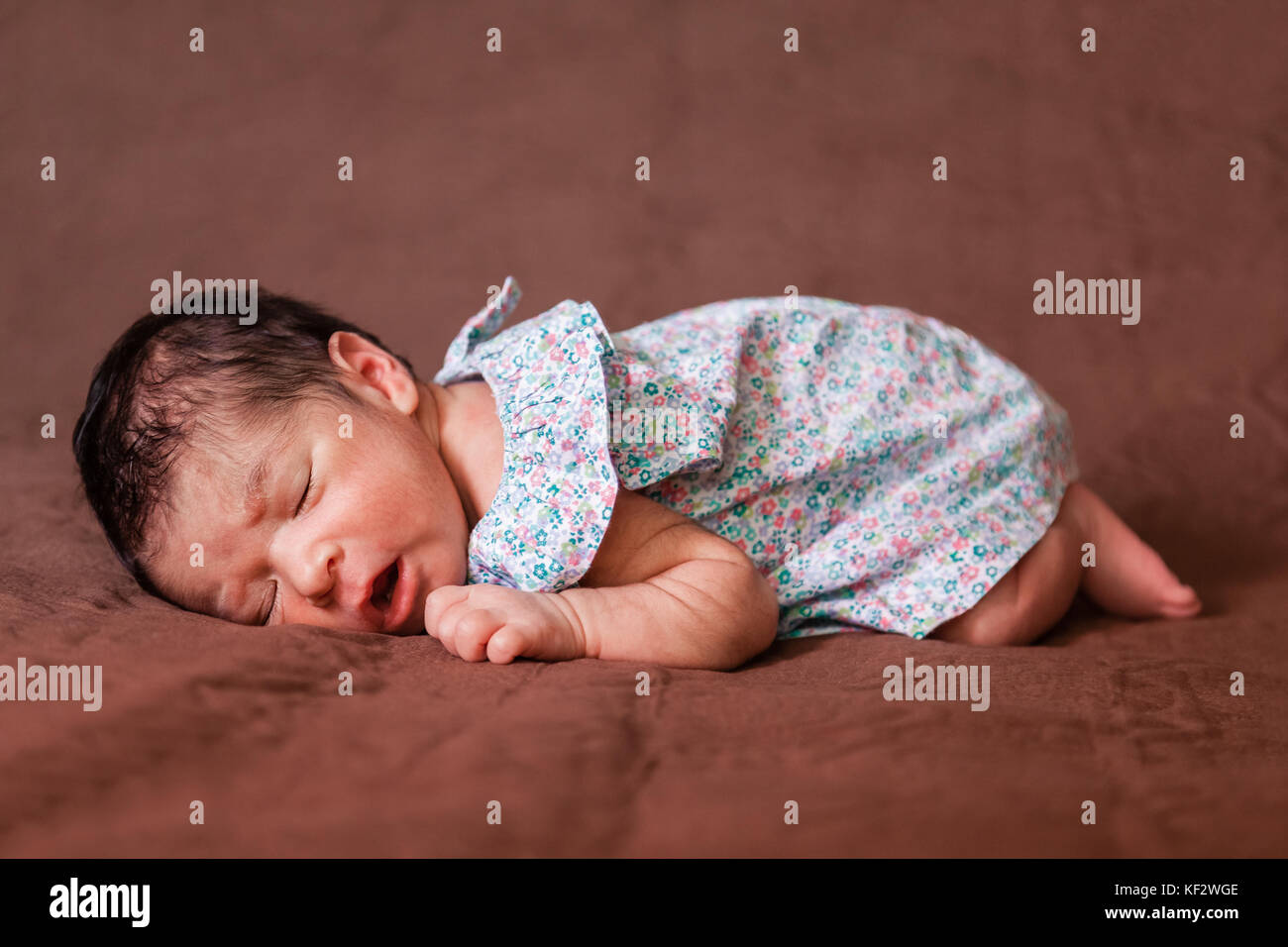 Cute two weeks old newborn baby girl wearing a floral dress, sleeping peacefully in bed in fetal position / newborn - Stock Image
