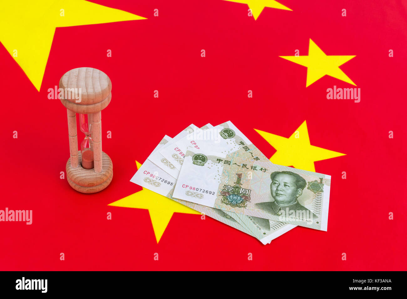 Chinese flag + small egg timer & Yuan banknotes. Metaphor Chinese growing debt problem / crisis, China time running Stock Photo