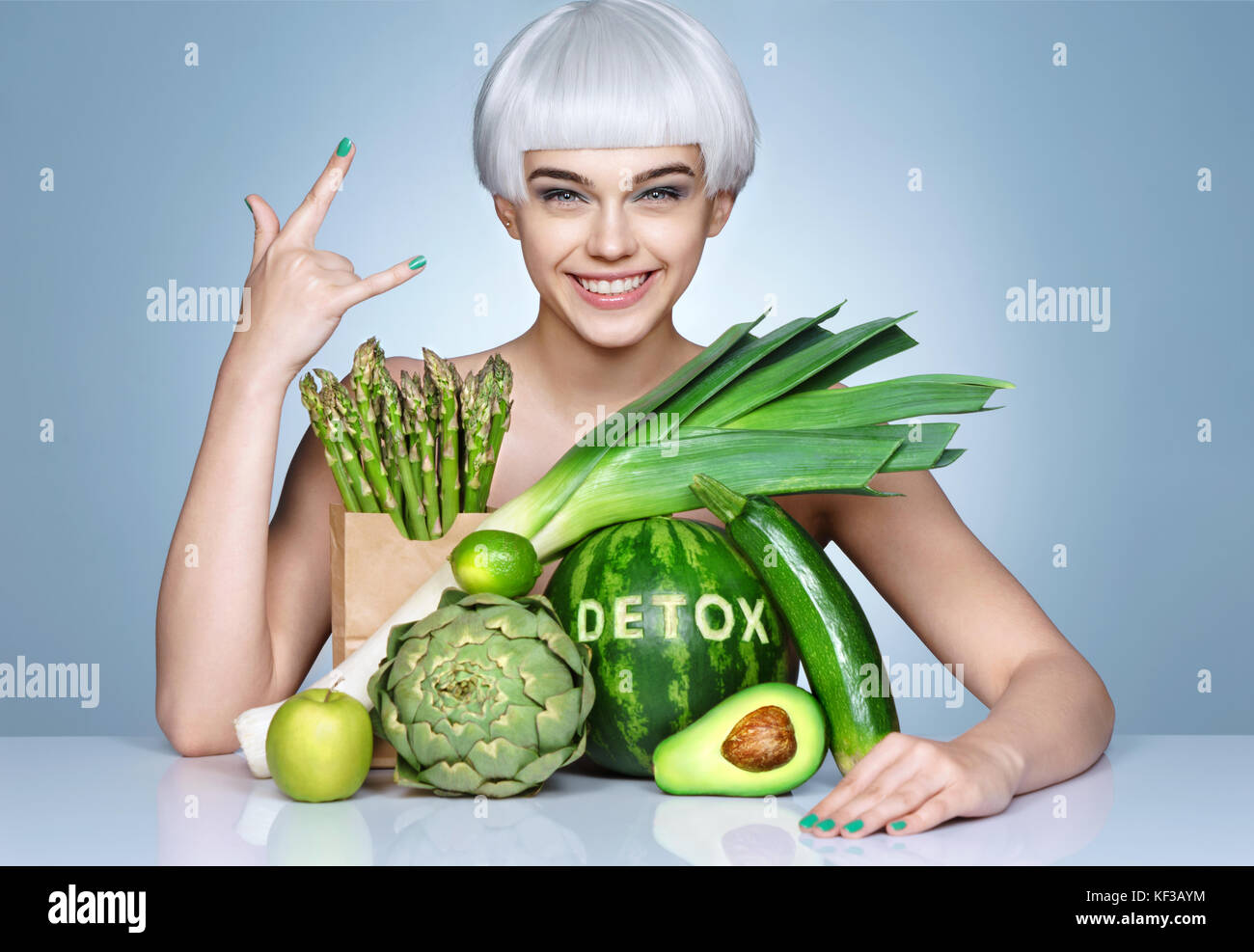 Fashion girl with an abundance of fruits and vegetables. Photo of smiling blonde girl showing gesture 'is cool'. - Stock Image