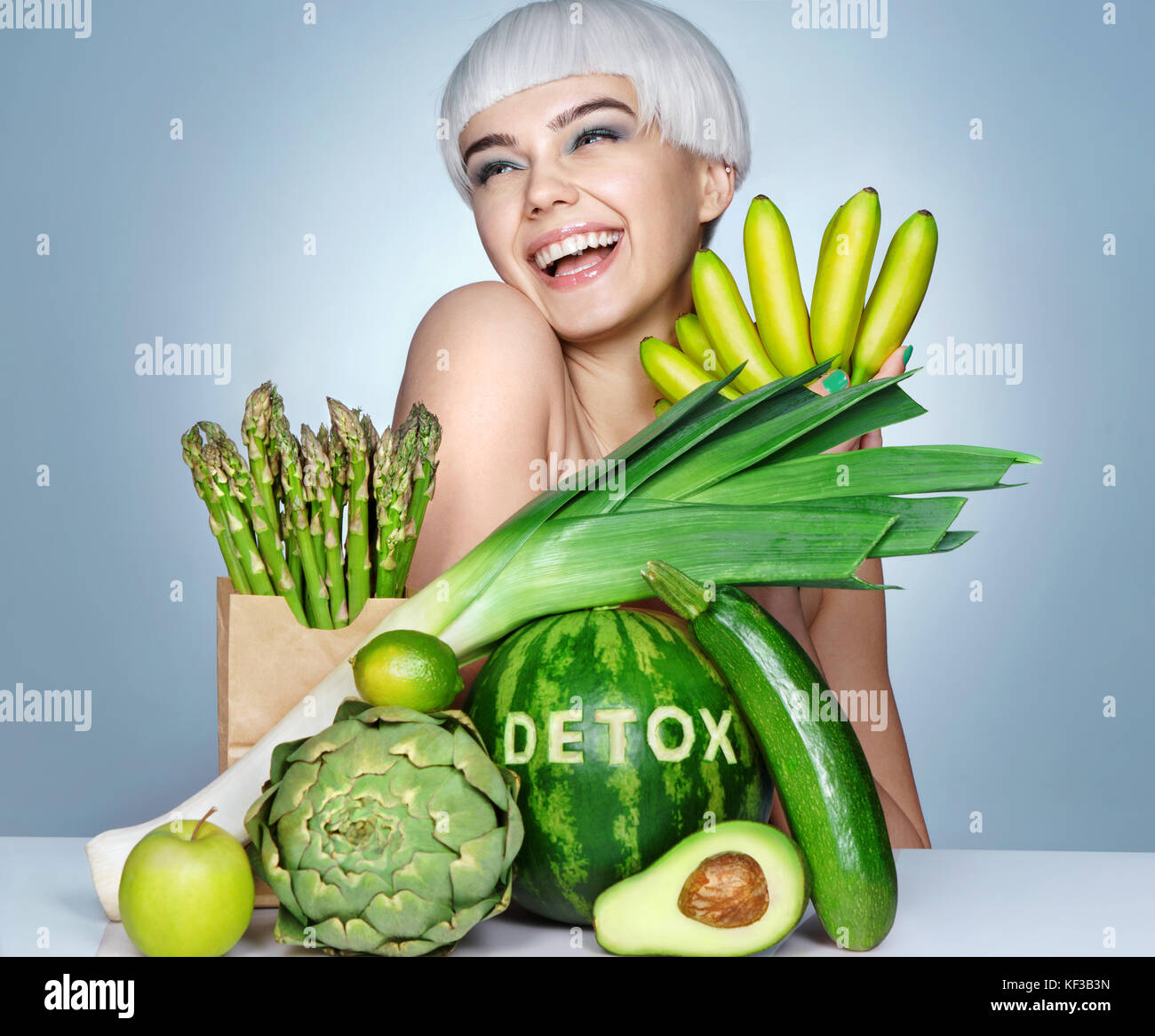 Happy young girl with an abundance of fruits and vegetables. Photo of smiling blonde girl on blue background. Healthy - Stock Image