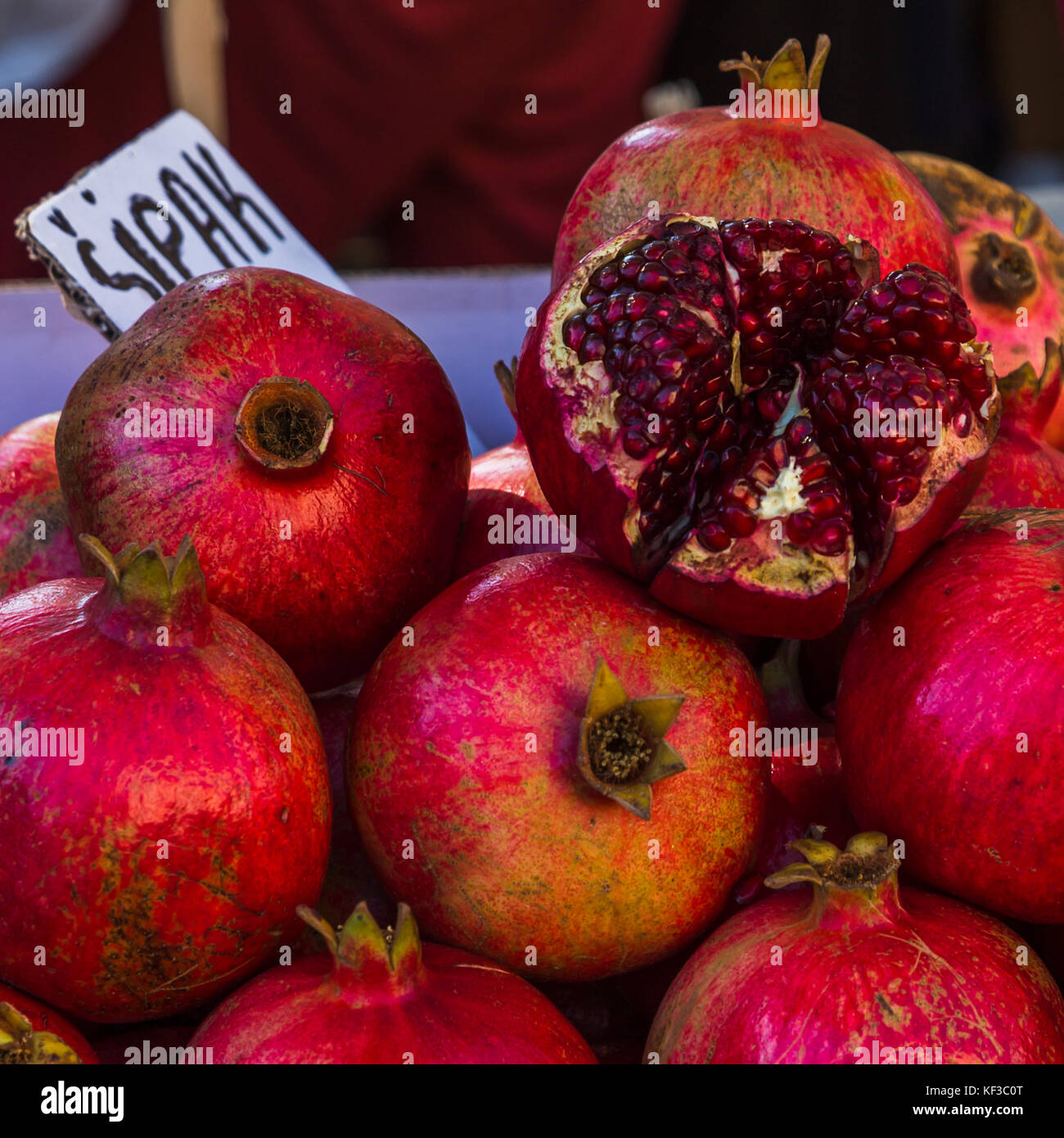 A tight square crop of a pile of pomegranate fruit seen on the green market in Split - the city's main fruit - Stock Image