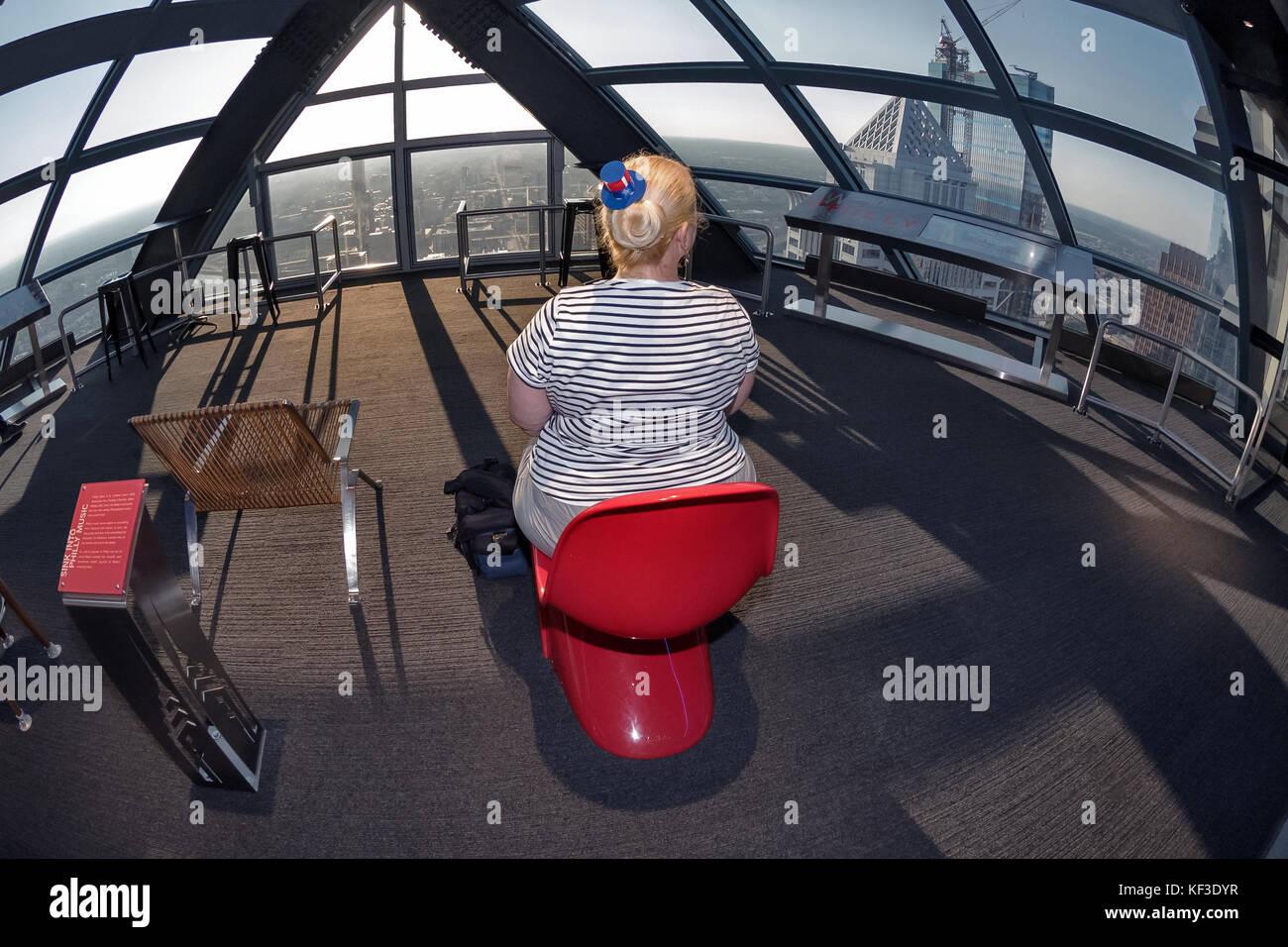 Tourist woman sitting on red chair, One Liberty Observation Deck,  Philadelphia, Pennsylvania, USA,  Philadelphia, - Stock Image