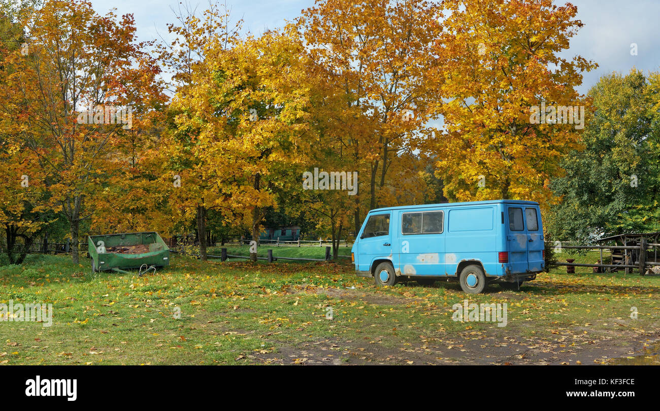 Old defective  no name cars are forgotten in a dump in an autumn forest. Panoramic landscape from several outdoor - Stock Image