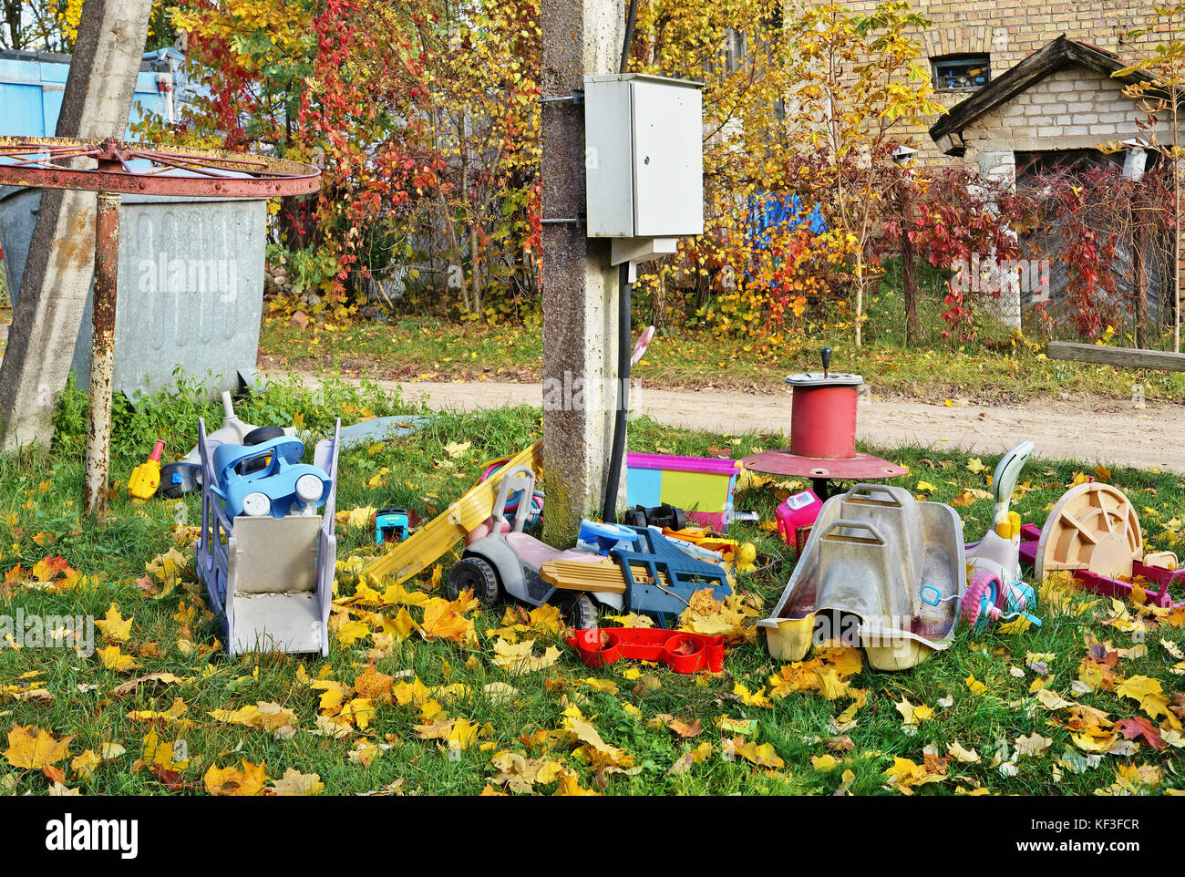 Old broken forgotten outdoor  no name  children toys on autumn village lawn near electrical box. Golden maple leaves - Stock Image