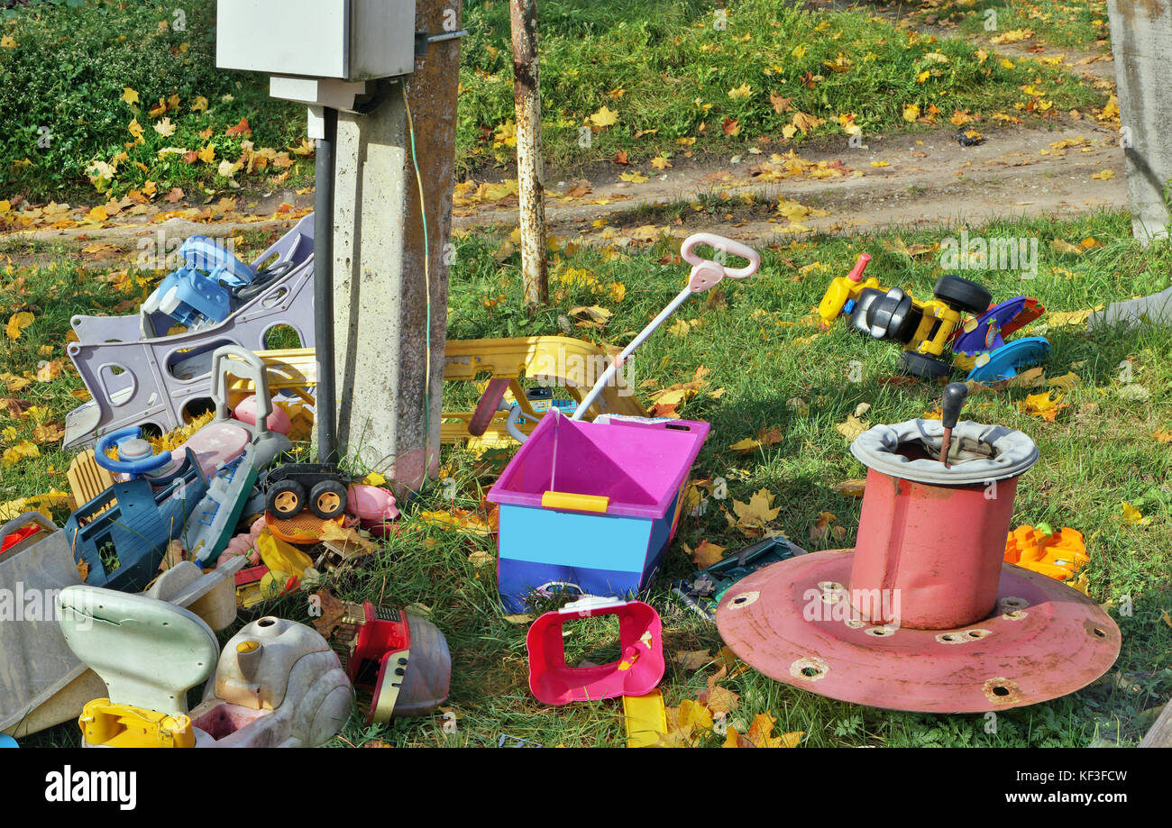 Old broken forgotten outdoor  no name  children toys on autumn lawn. Golden maple leaves on green grass. Sunny day - Stock Image