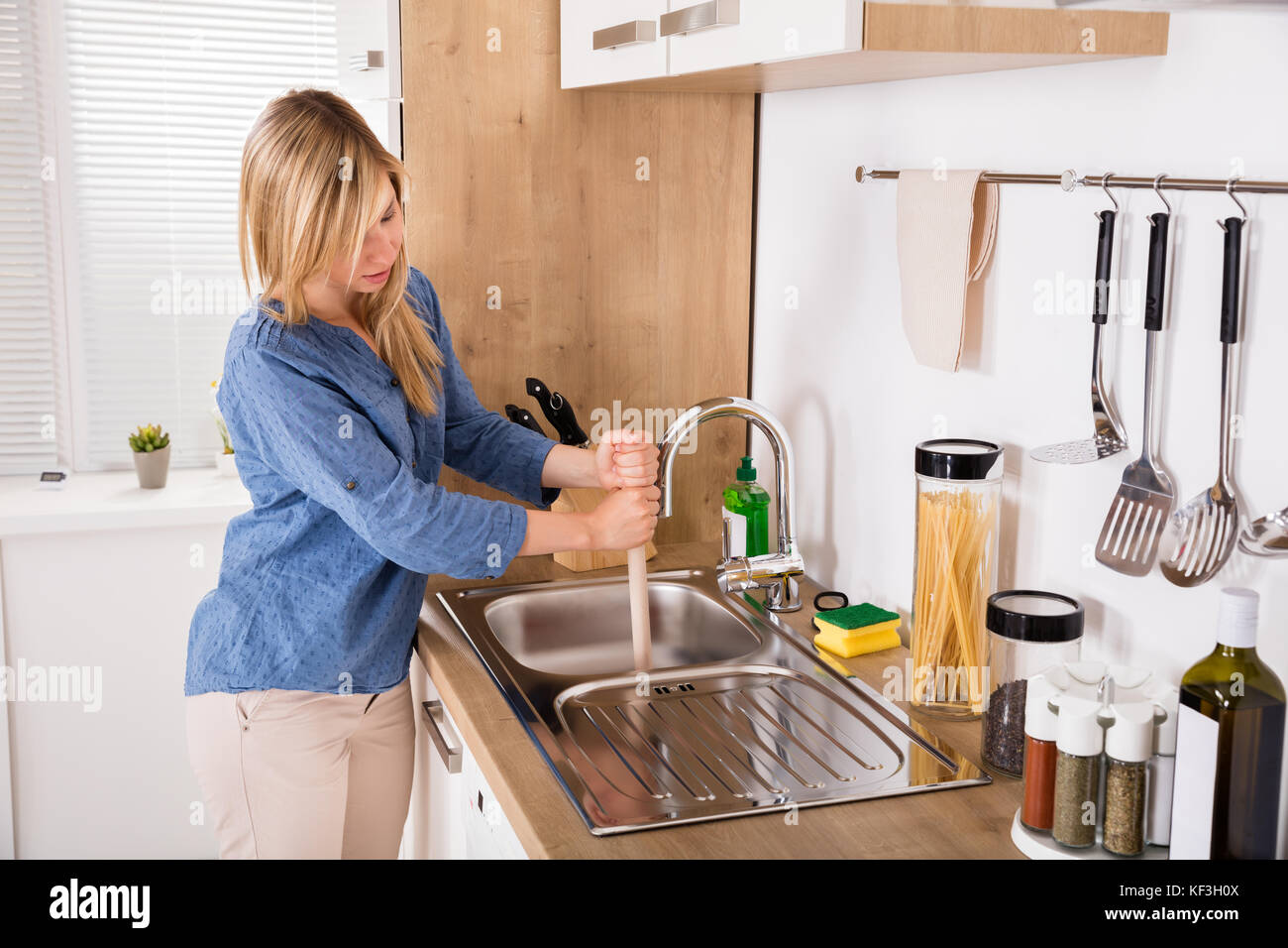 Young Woman Using Plunger In Blocked Kitchen Sink To Unclog Drain At on unclog sinks both kitchen, unclog tub drain with bleach, unclog pipes, unclog my bathroom sink, unclog sink drain, toilet plunger,