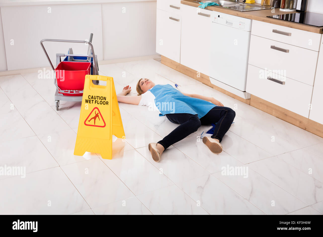 Young Fainted Housemaid Lying On Floor In Kitchen. Accident Compensation Concept - Stock Image