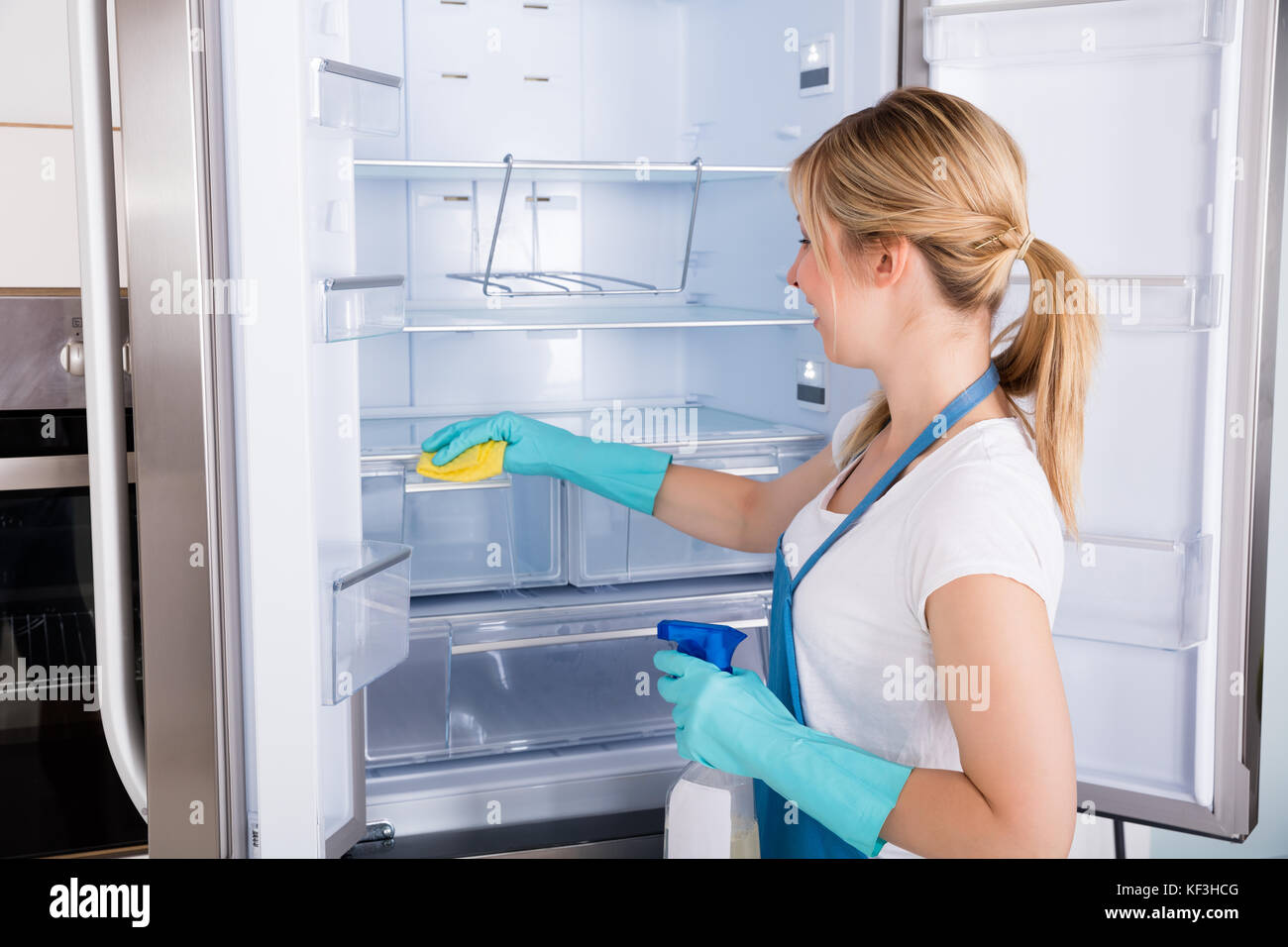 Young Smiling Professional Janitor Woman Cleaning Empty Refrigerator In Kitchen - Stock Image