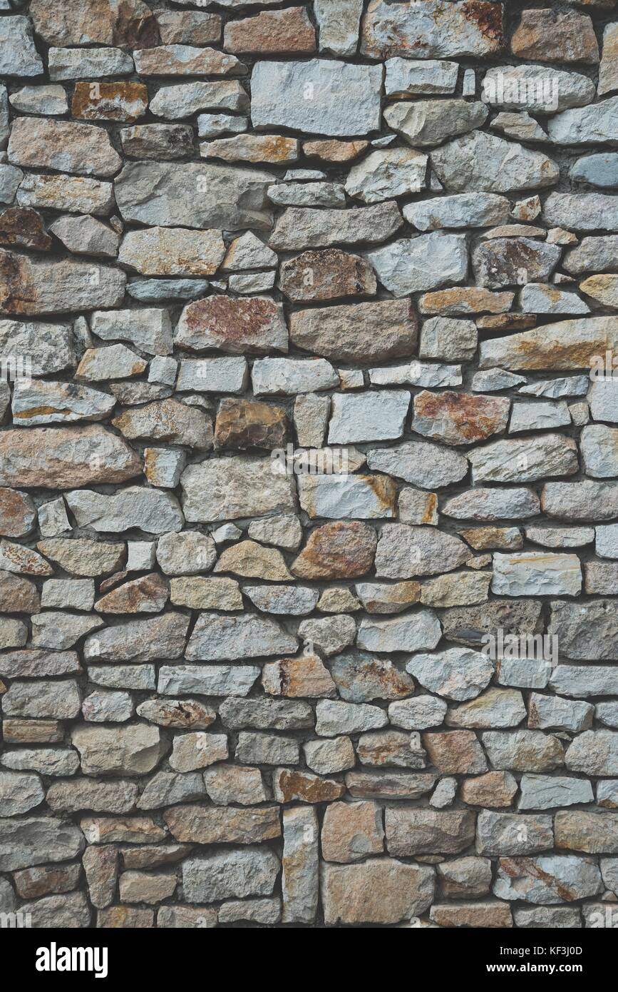 Stone wall background of colorful stones with matt film effect. Vertical photo - Stock Image
