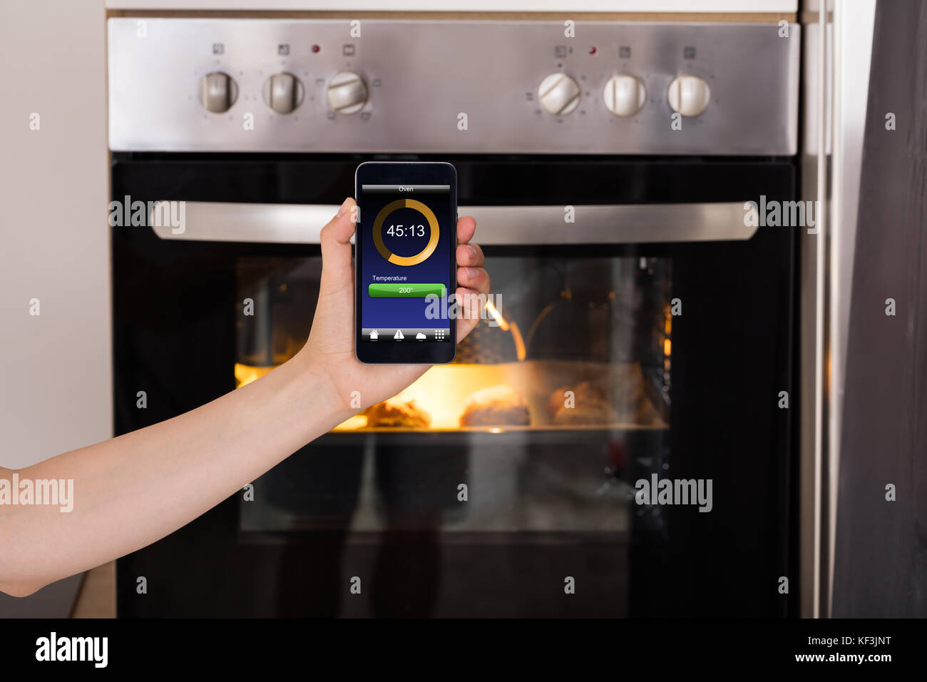 Close-up Of Person Hands Operating Oven Appliance With Mobile Phone App - Stock Image