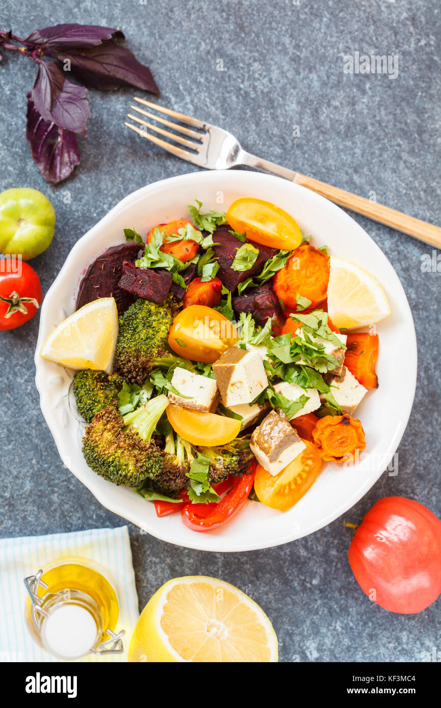 Vegetarian salad of baked vegetables and tofu, top view, dark background. - Stock Image