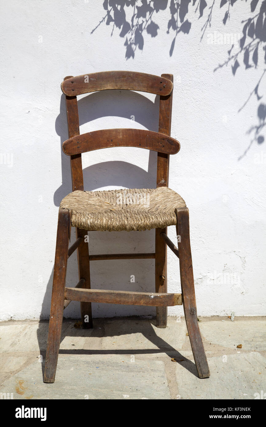 simple vintage wooden and cane chair, Skopelos island, Aegean Sea, Greece Stock Photo