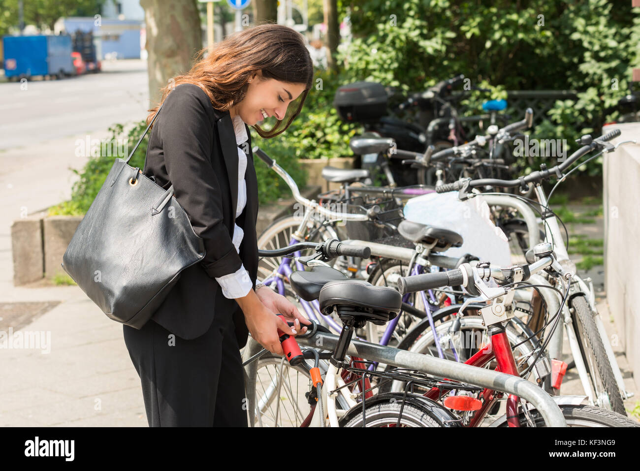 Smiling Young Businesswoman With Handbag Locking Up Her Bicycle - Stock Image