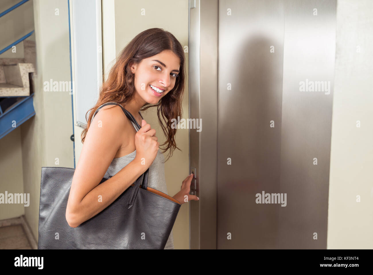 Smiling Young Woman With Handbag Using Elevator Stock Photo