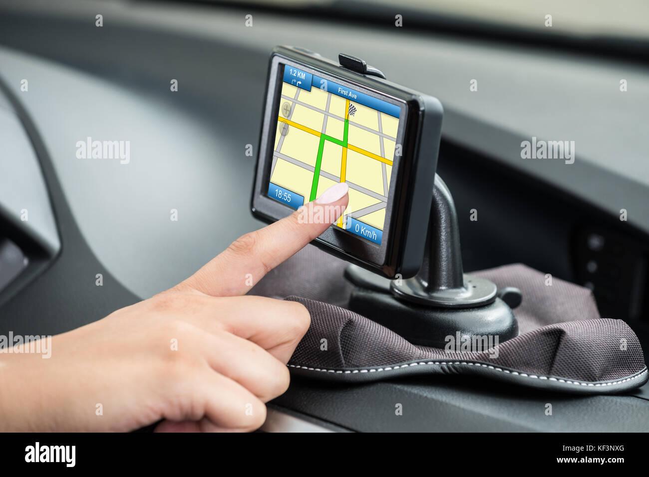 Close-up Of Female's Hand Using GPS Navigation Inside Car - Stock Image