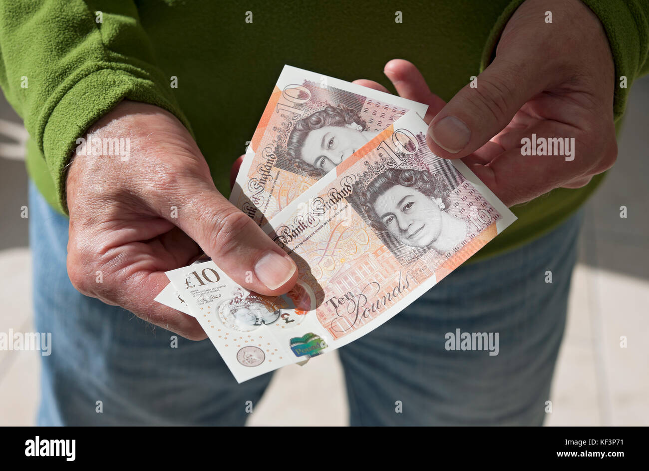 Man holding new polymer ten pound notes England UK United Kingdom GB Great Britain - Stock Image