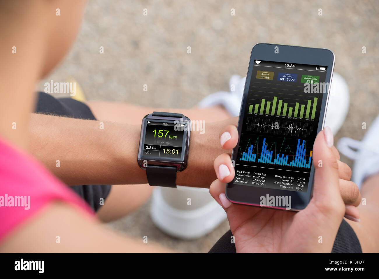 Female Runner Looking At Her Mobile And Smart Watch Heart Rate Monitor - Stock Image