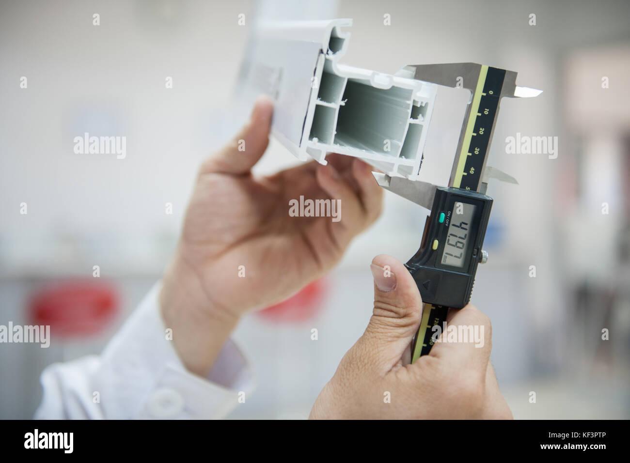 the laboratory technician measures the plastic profile with a digital caliper. application of digital caliper close - Stock Image