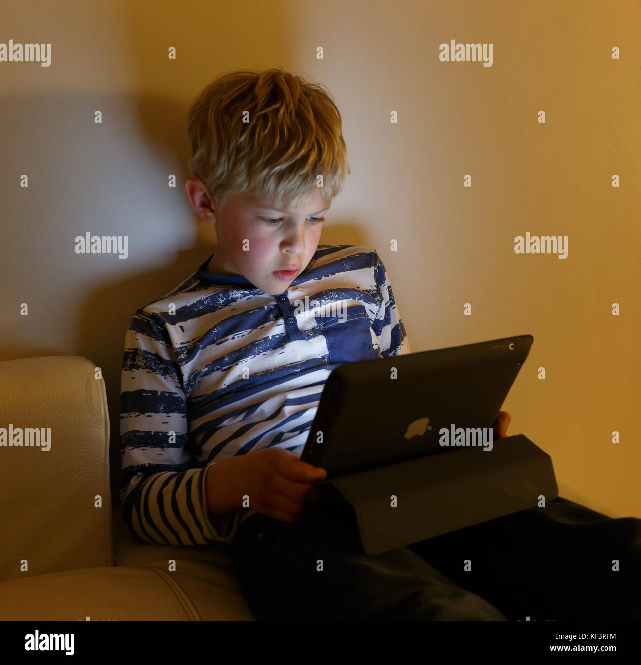 Boy watching Ipad and face is lit by the screen - Stock Image