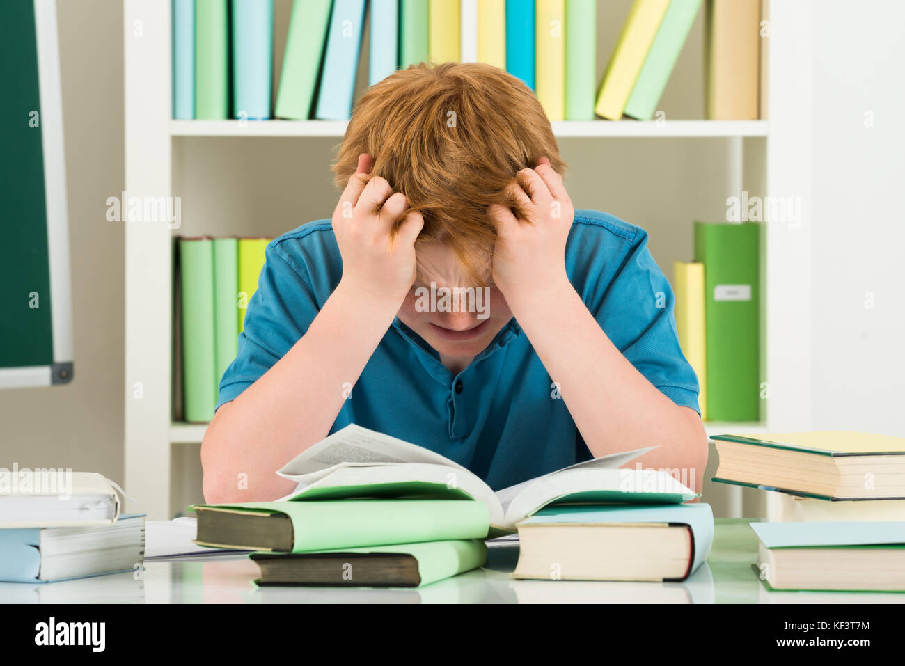 Exhausted Boy Studying In Library With Books On Desk Stock Photo
