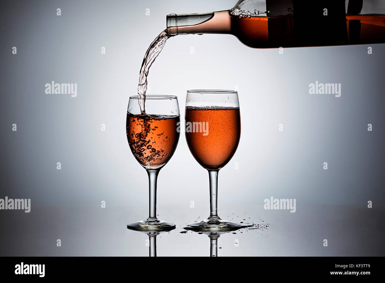 Pouring rose' wine form a bottle into wine glasses. - Stock Image