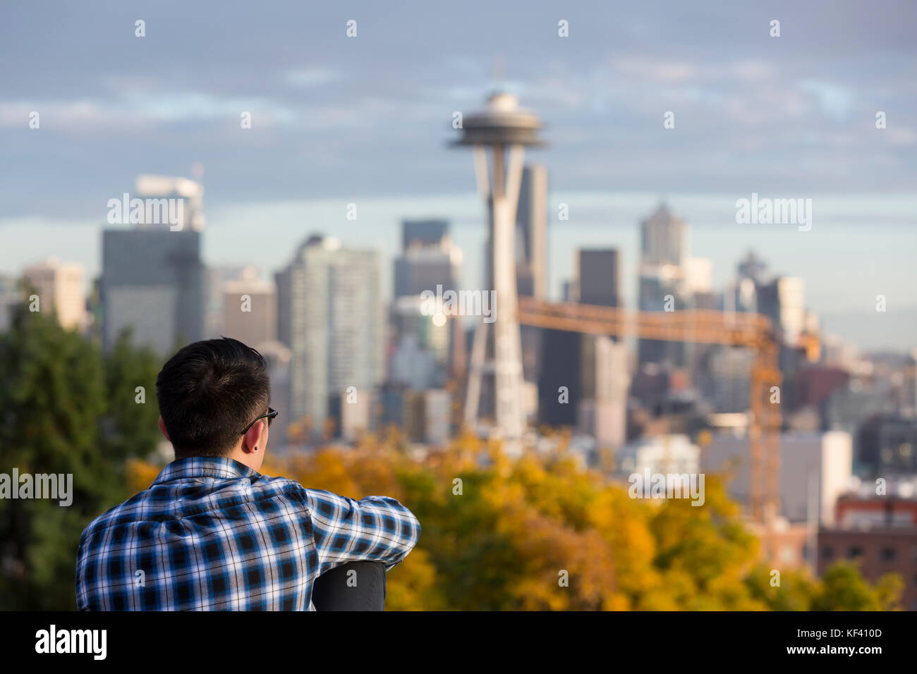 Seattle, Washington: A young man looks out to the Space Needle from Kerry Park. Space Needle LLC officially started - Stock Image