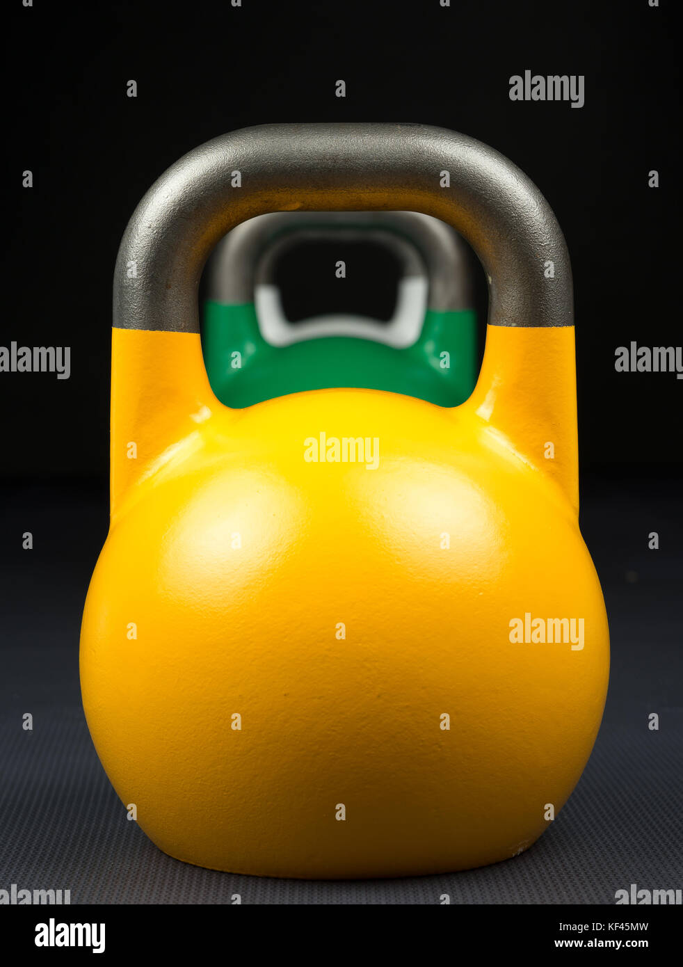 Yellow, green and white competition kettlebells lined up in a row on a weight training gym floor. - Stock Image