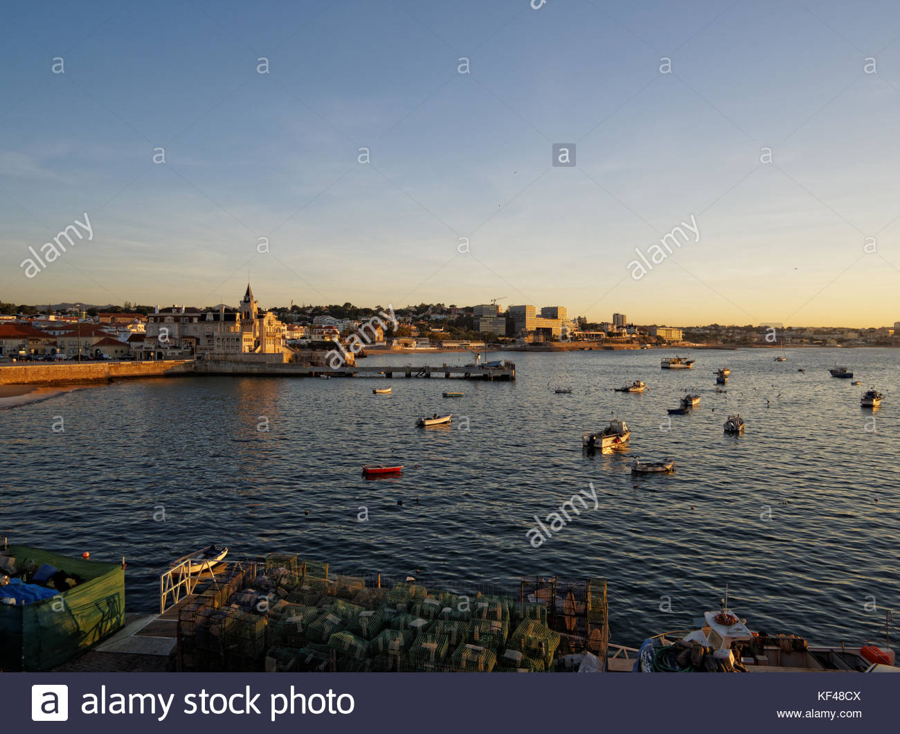 Fishing boats at anchor, lobster pots, Cascais Bay at sunrise, Portugal - Stock Image