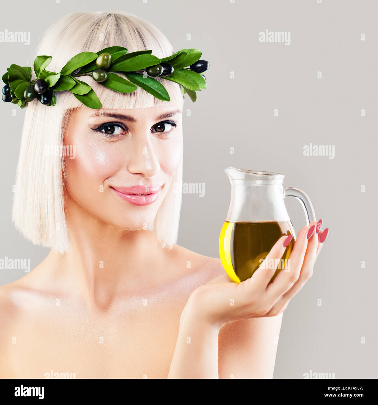 Beautiful Woman with Green Olive Leaves Wreath and Glass Bottle of Organic Olive Oil. Healthy Eating and Mediterranean - Stock Image