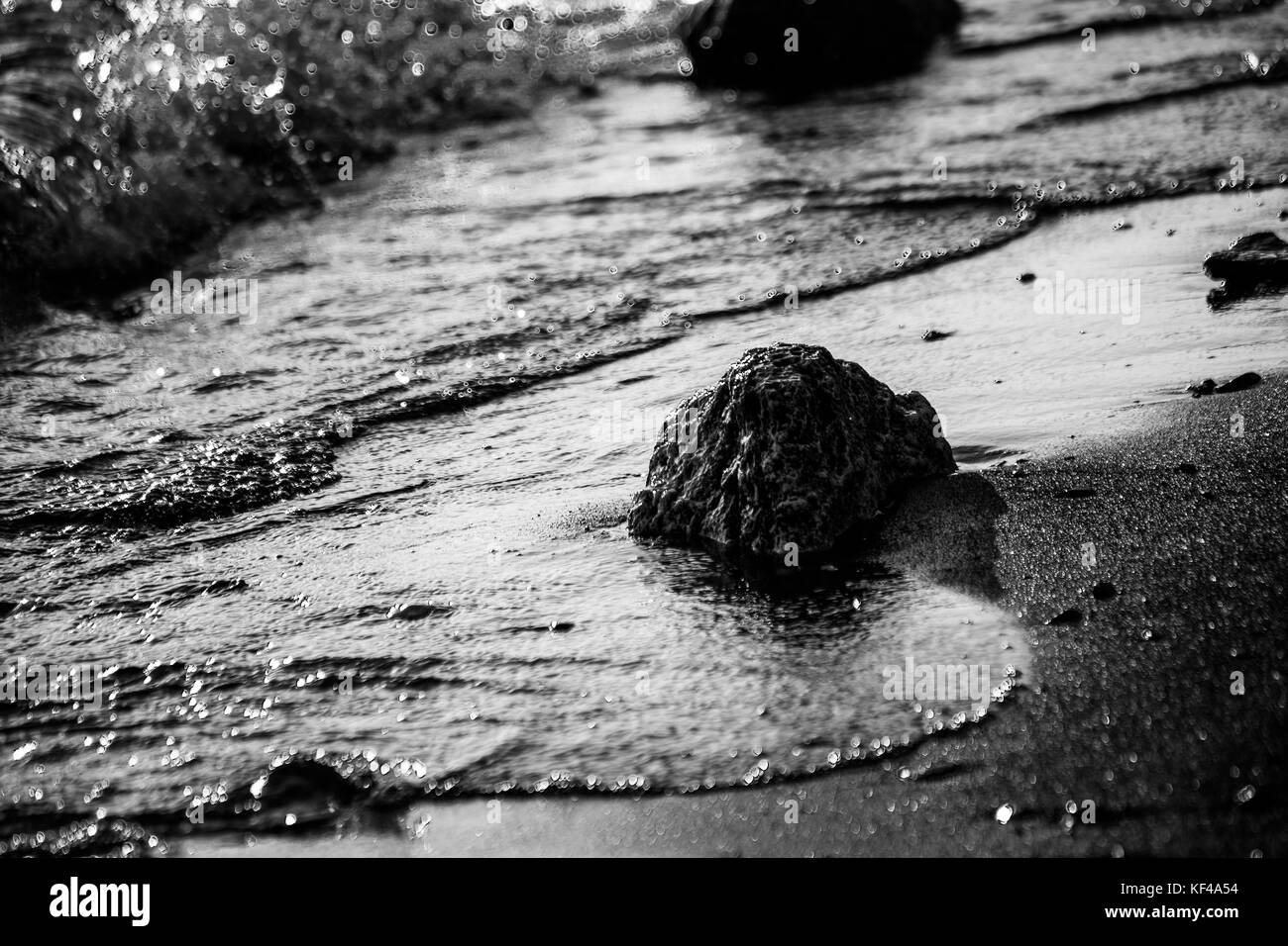 A close view of a lake shore, with details of water bubbles and stones and pebble on the sand - Stock Image