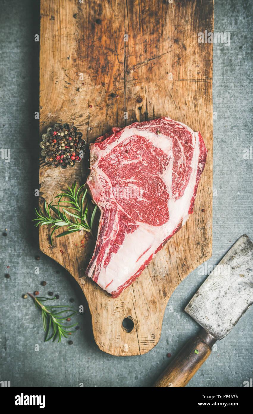 Raw beef steak rib-eye on board with seasoning, copy space - Stock Image