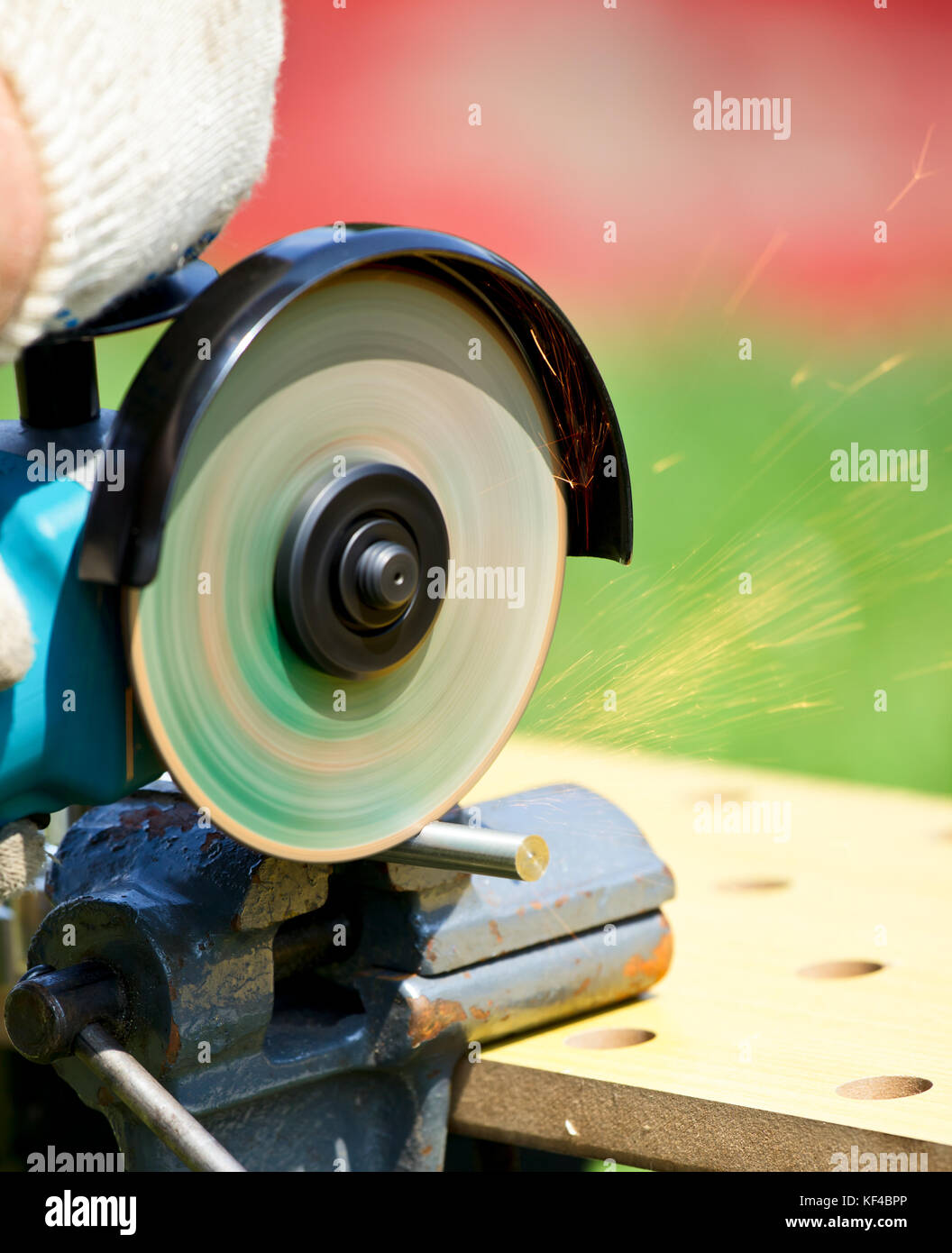Man cutting metal with angle grinder outdoor - Stock Image