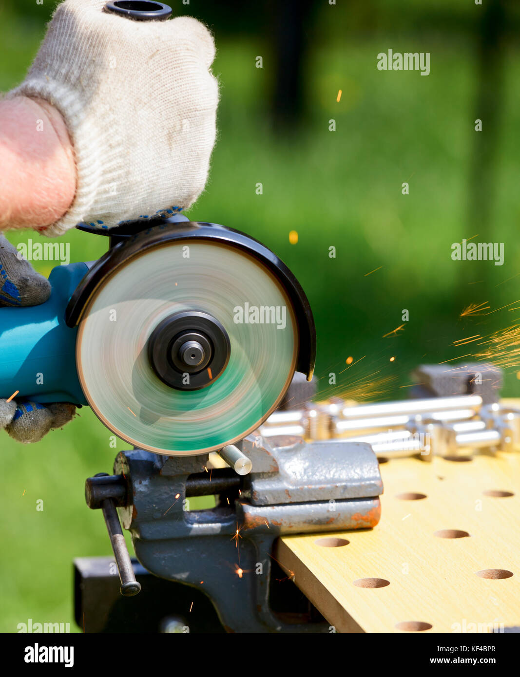 Man cutting metal with angle grinder - Stock Image