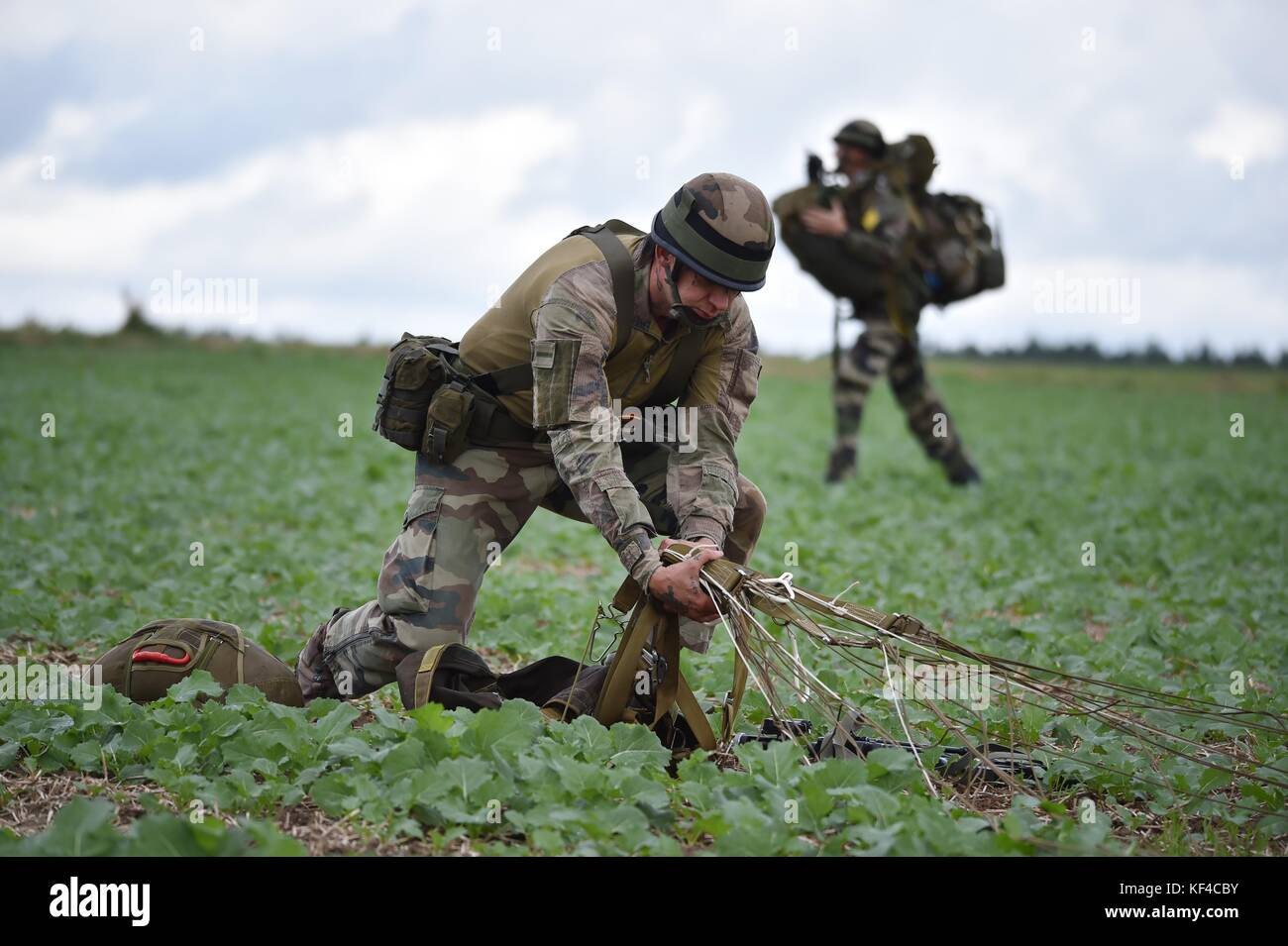 A French soldier recovers his parachute after an airborne operation during Exercise Swift Response near the Joint - Stock Image