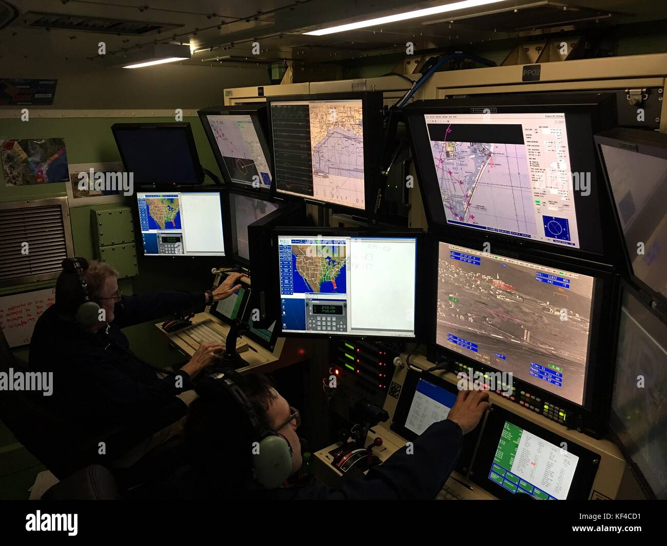 U.S. Customs and Border Protection agents operate an unmanned aircraft system from a control room to collect radar - Stock Image