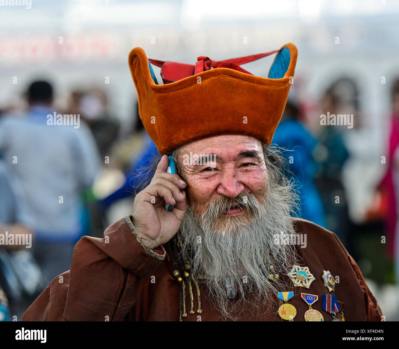 Elderly man with beard, head-dress and medals is talking on a mobile phone, Ulaanbaatar, Mongolia - Stock Image