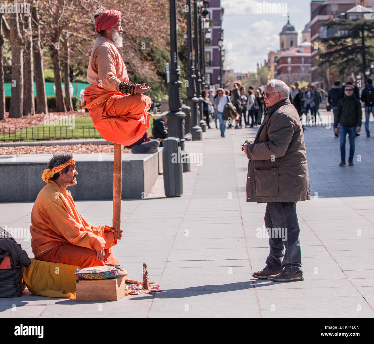 Indian Street Entertainers in meditative pose and orange clothing with tourists watching in Madrid Spain, Europe. - Stock Image