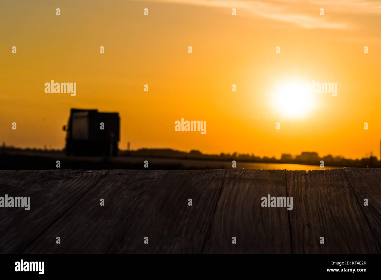 Empty rustic wood table top with motion blurred truck at sunset background. Can montage or display your products. & Empty rustic wood table top with motion blurred truck at sunset ...