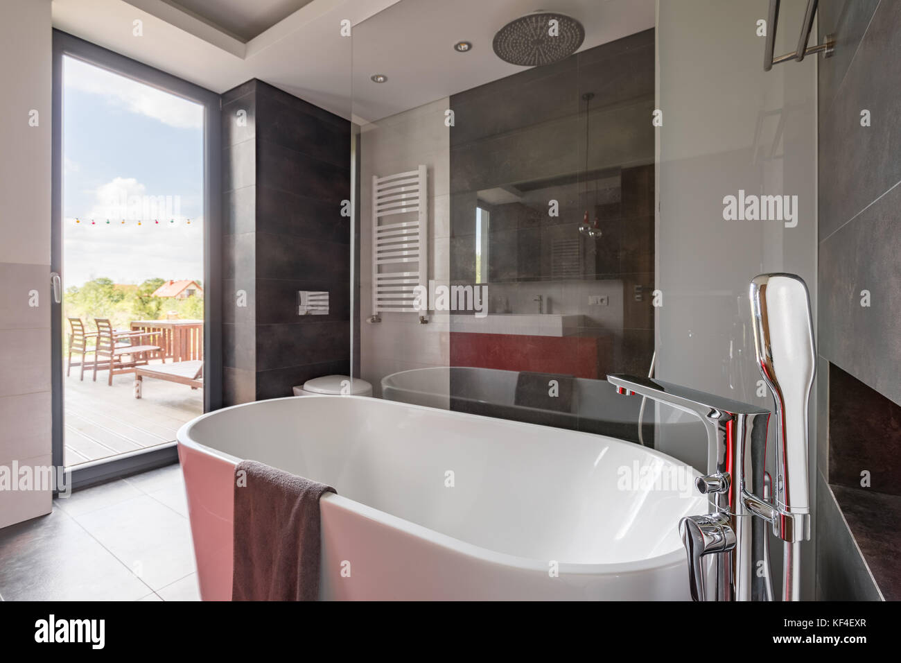 Luxurious bathroom with big bathtub and balcony door Stock Photo ...