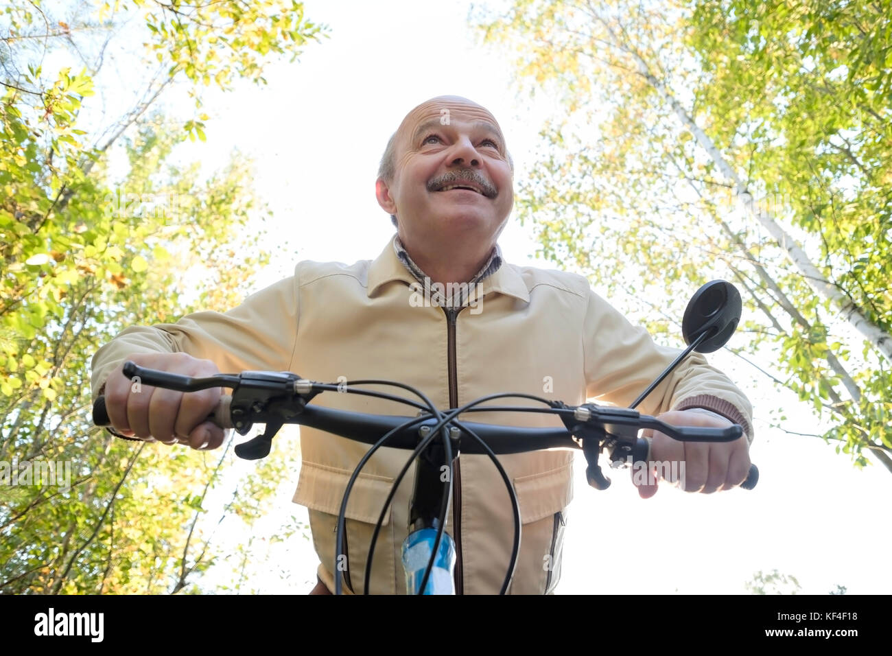 Senior caucasian man on cycle ride in countryside. Green trees on background. He is happy and active. - Stock Image