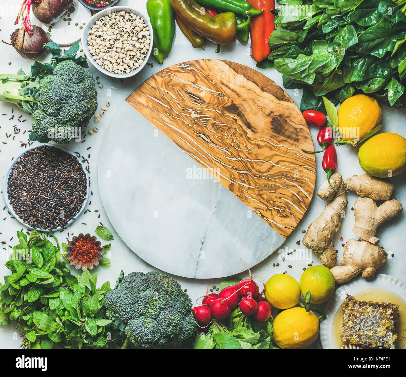 Clean eating healthy cooking ingredients with round board in center - Stock Image
