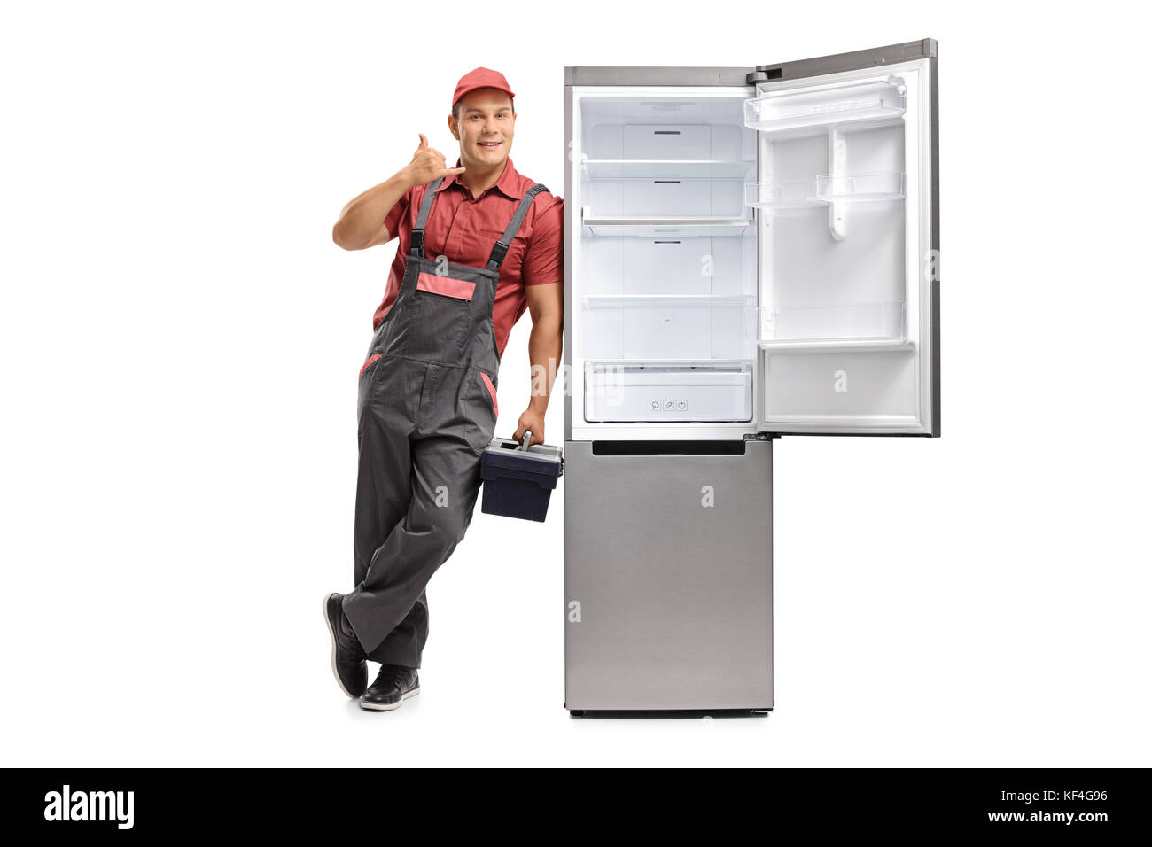 Full length portrait of a serviceman leaning against an empty fridge and making a call me gesture isolated on white - Stock Image