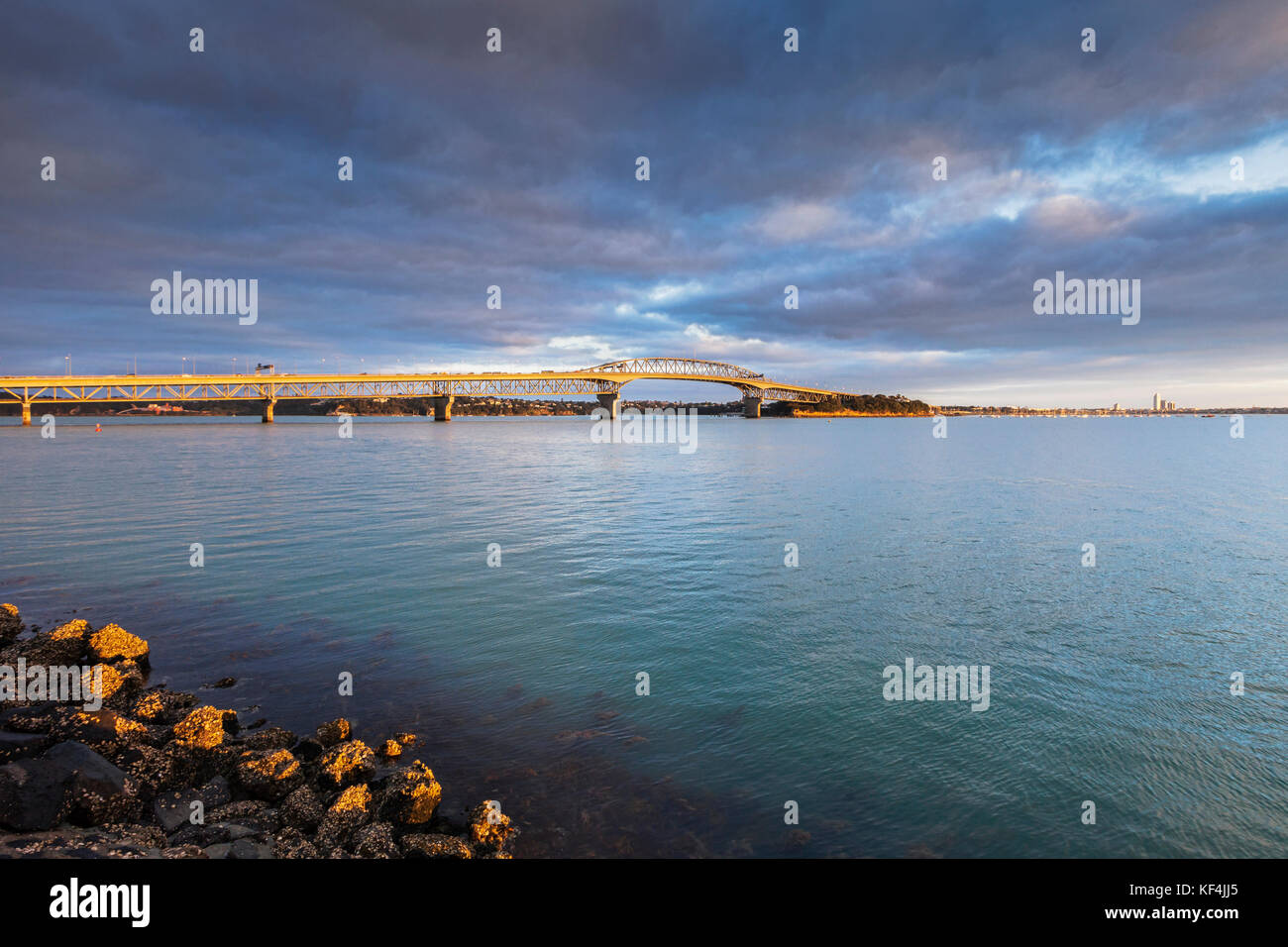 Auckland Harbour Bridge at sunrise under a dramatic moody sky. - Stock Image