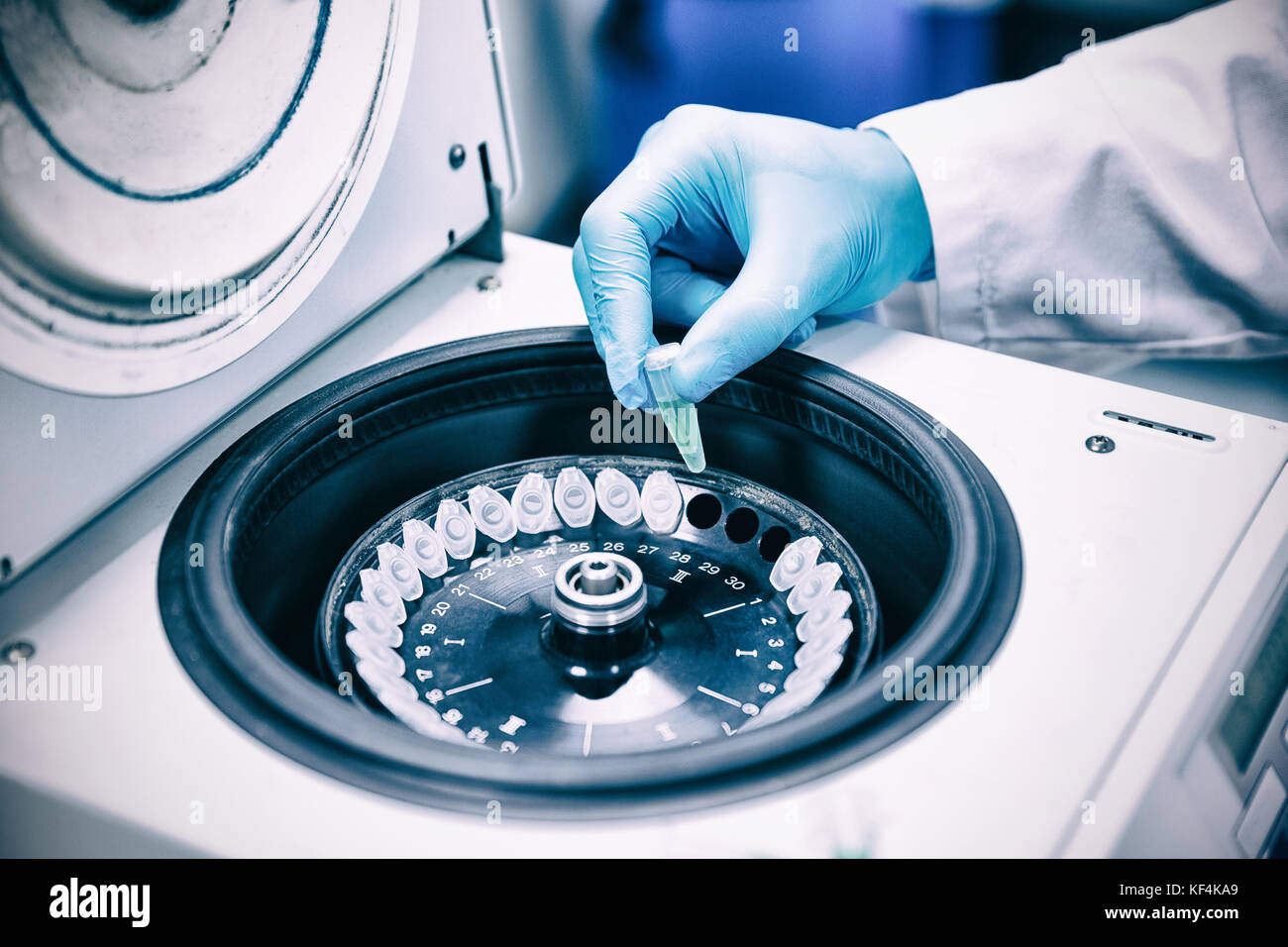 Close up of a chemist using a centrifuge in lab - Stock Image