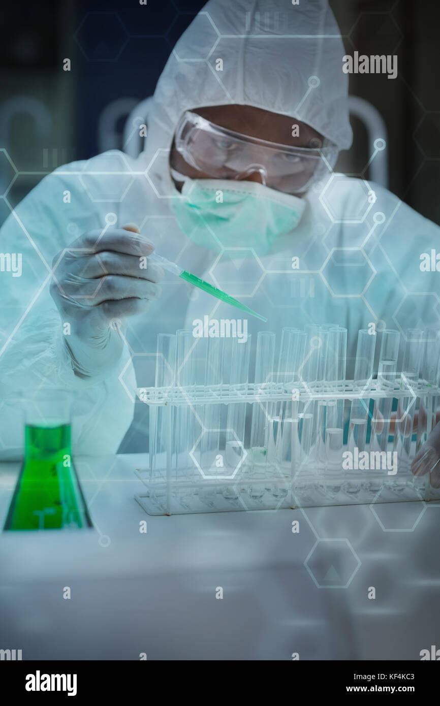 Digital data  against chemist adding green liquid to test tubes - Stock Image