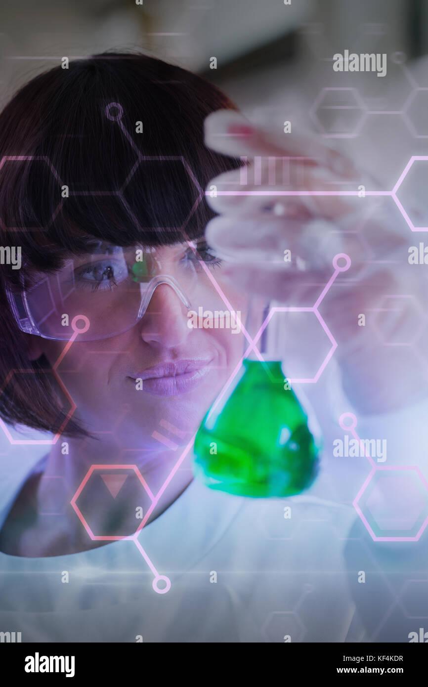 Digital data  against chemist holding up beaker of green chemical - Stock Image