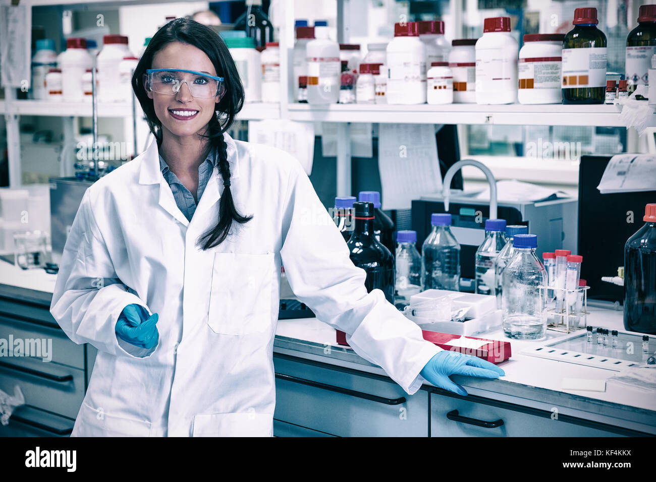 Portrait of a smiling chemist leaning against desk in the laboratory - Stock Image