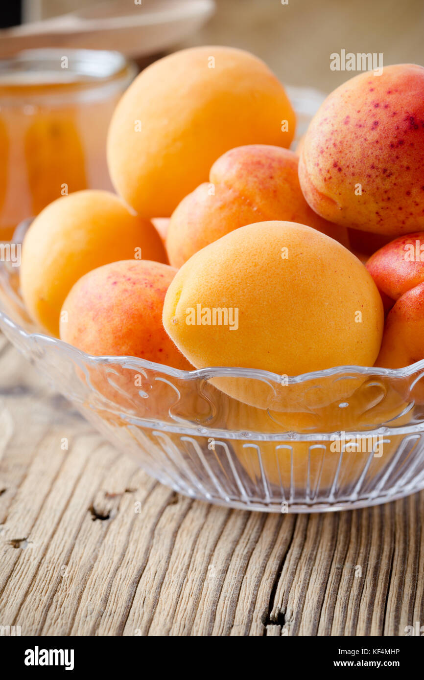 Fresh organic apricots in glass bowl on wooden board - Stock Image